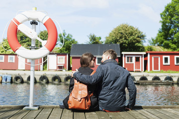 Rear view of couple sitting at harbor
