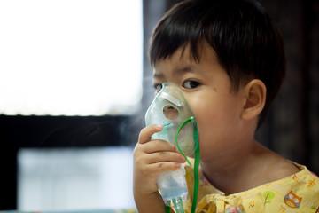 little boy wearing oxygen mask in hospital ward