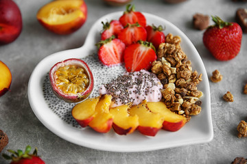 Healthy breakfast with fruits and chia seeds in heart shaped plate