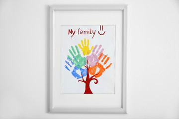 Family hand prints in frame on wall