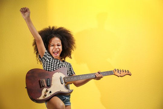 Afro-American little girl with curly hair playing guitar on yellow background