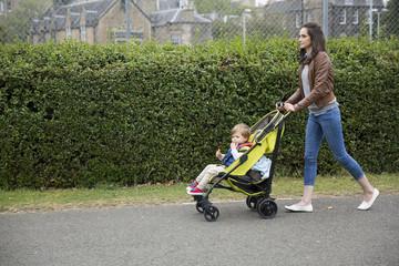 Mum walking with toddler in pram.
