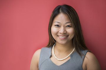 Asian businesswoman leaning against a red wall.