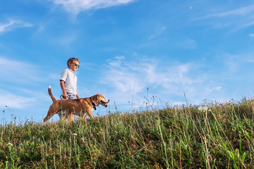Fototapete - Boy with dog walk together on green hill