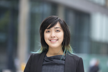 Asian businesswoman in smart business suit standing outside.