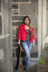 Filipino woman holding skateboard and leaning against a wall.
