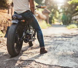 Young man on his motorcycle on dirt road