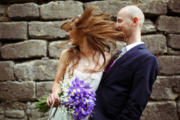 Groom hugs a bride while she plays with her hair