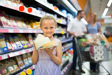 Girl holding cheese in hands in supermarket.