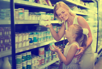Portrait of woman and girl holding yogurt