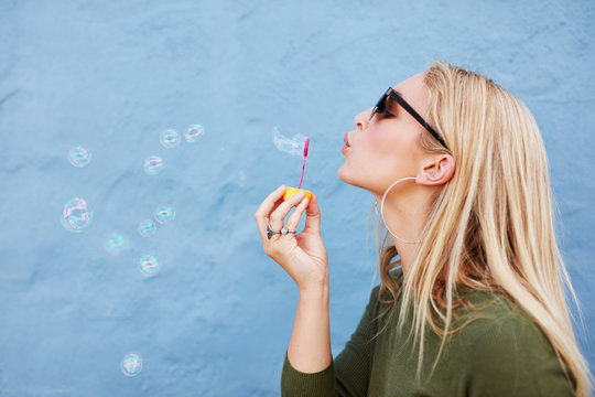Attractive female blowing soap bubbles