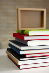 stack of new books with wooden photo frame