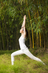 Chinese woman practicing yoga outdoors.