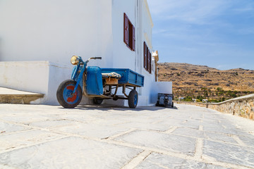 Blue tricycle scooter in front of stone wall