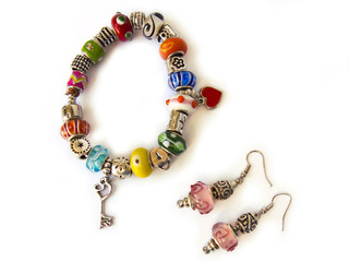 Beads and gems bracelet, and a pair of earrings, isolated in white