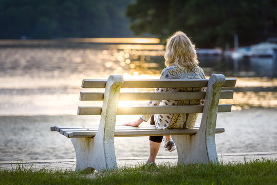 Woman sitting on a bench watching the sun set at a lake on the beach