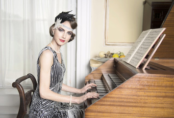 Pretty brunette in twenties theme sequinned dress sitting at harpsichord making eye contact with a nice smile