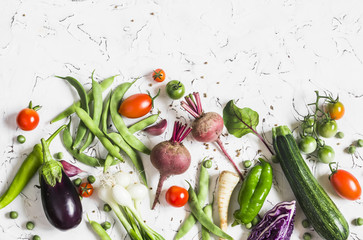Food background. Assortment of fresh vegetables on a light background - zucchini, eggplant, peppers, beets, tomatoes, green beans, red cabbage. Free space for text, top view