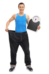 Guy in large jeans holding a weight scale