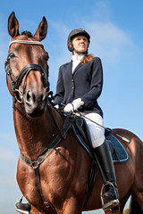 Portrait of serious beautiful young girl jockey in uniform sitting on a horse against blue sky and yellow field and looking forward on a sunny day. Equestrian sport - dressage.