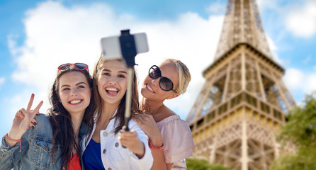 group of smiling women taking selfie in paris