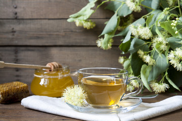 Linden tea in glass cup and jar with honey with linden flowers on a dark wooden background