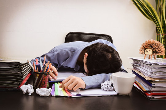 Businessman asleep at office desk with finance sheet calculator and coffee. concept for overworked Dark vintage tone