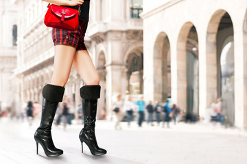 Wall Mural - Woman with black long high heels boots,handbag purse and shorts walking in the city.