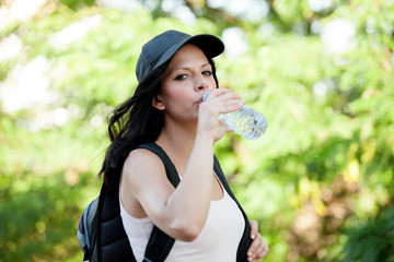 Beautiful woman drinking water while hiking