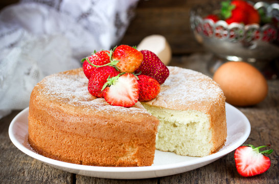 Victoria sponge cake with strawberry on old wooden background