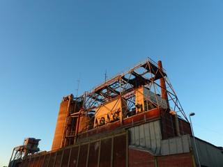 Stillgelegte alte Fabrikanlage mit Silo im Licht der untergehenden Sonne vor strahlend blauem Himmel am alten Hafen von Münster in Westfalen im Münsterland