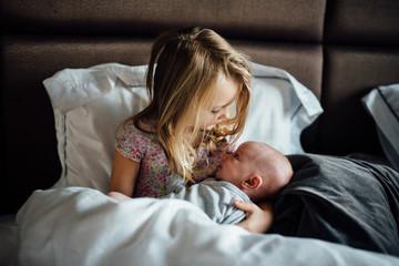 Girl holding baby sister, portrait