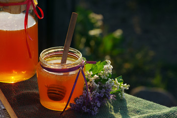 Honey in a glass jars and bee honeycombs with flowers melliferous herbs against flowers and greens. Honey with flowers.