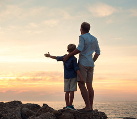 Father and son looking on sunset at the sea