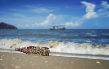 sea acorn colony on a brown glass bottle dumped pollute at the sand beach,blurred splash of sea wave and blue sky in background,filtered image,selective focus