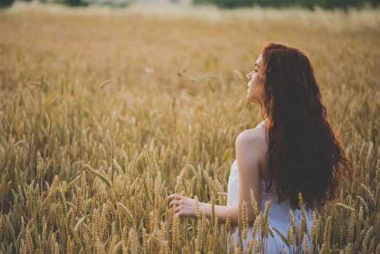 Portrait of beautiful girl with red-hair on rye field at sunset