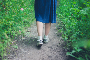 Feet and legs of woman walking in forest