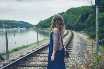 Woman walking by railroad tracks and river