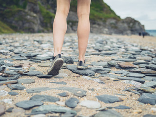 Legs and feet of woman walking on beach