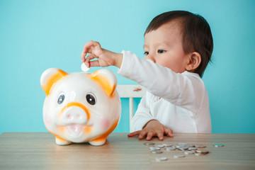 little baby moneybox putting a coin into a piggy bank - kid savi