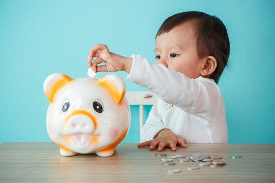 little baby moneybox putting a coin into a piggy bank.