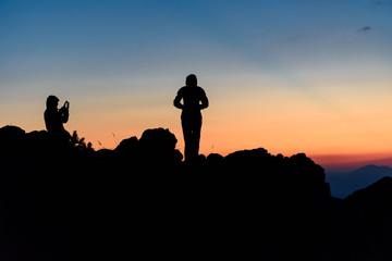 Silhouette of a couple taking self portraits, enjoying the sunset at Vitosha Mountain, Bulgaria