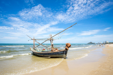 Old fishing boat and deep bluesky background at Hua Hin beach, Prachuap Khiri Khan Province, Thailand.