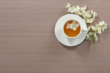 Cup of tea with jasmine flowers on wooden background