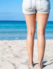 woman standing on sand beach. closeup detail of legs