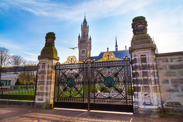 Gate of Peace Palace at Hague, Netherlands at sunset and bird symbol of news, flying