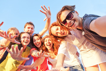 Group of happy young friends doing selfie against the blue sky. Wall mural