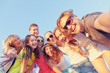 Group of happy young friends doing selfie against the blue sky.