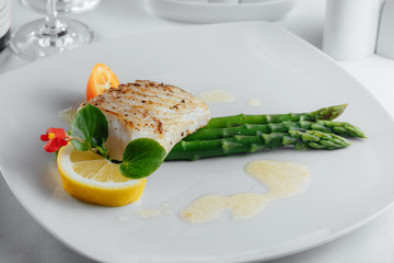 fish with a slice of lemon and asparagus on a white plate
