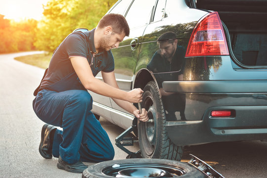 Auto mechanic changing  tire on car on road
